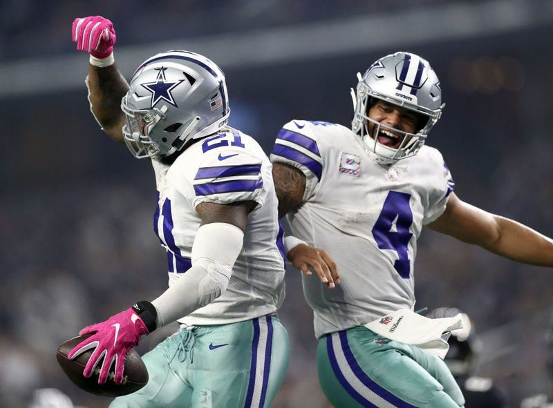 Ezekiel Elliott #21 and Dak Prescott #4 of the Dallas Cowboys celebrate the fourth quarter touchdown against the Jacksonville Jaguars at AT&T Stadium on October 14, 2018 in Arlington, Texas.