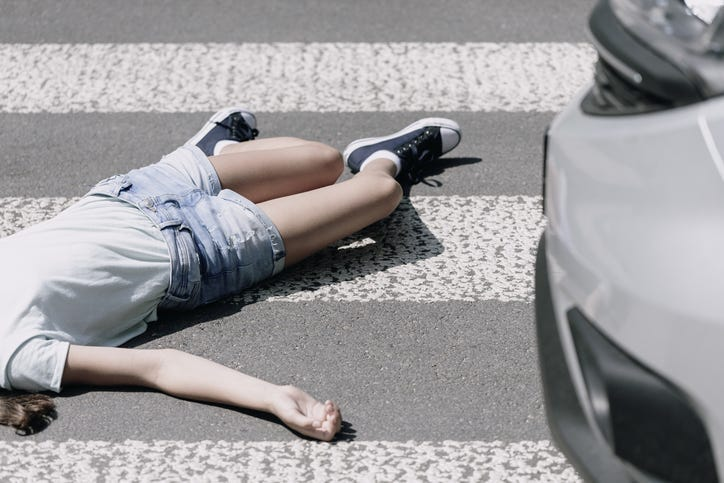 High angle on a child on a crosswalk hit by a car