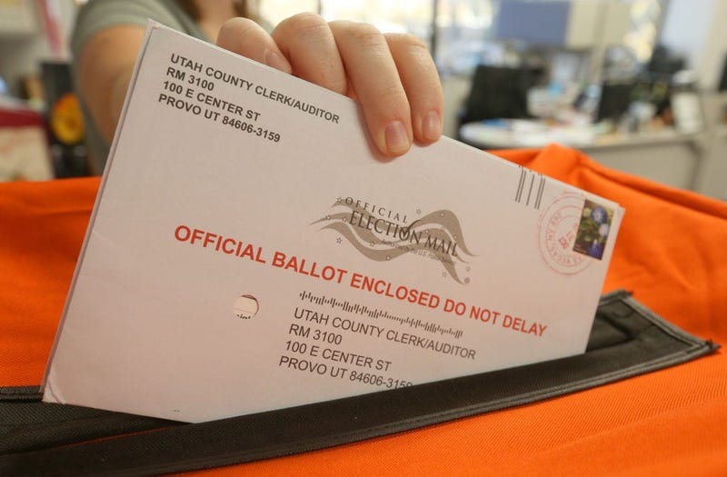 A employee at the Utah County Election office puts mail in ballots into a container to register the vote in the midterm elections on November 6, 2018 in Provo, Utah