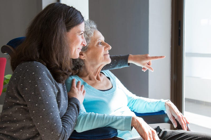Happy senior mother and adult daughter enjoying dramatic view out of window. Elderly lady resting in armchair, while young woman pointing out of window.
