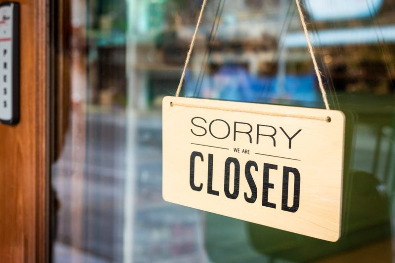 sorry we're closed sign hangs on a door to a business