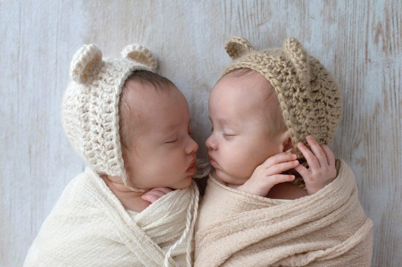 Profile headshot of two, fraternal, twin, baby girls sleeping. They are wearing crocheted bear hats and are swaddled in cream and tan wraps.