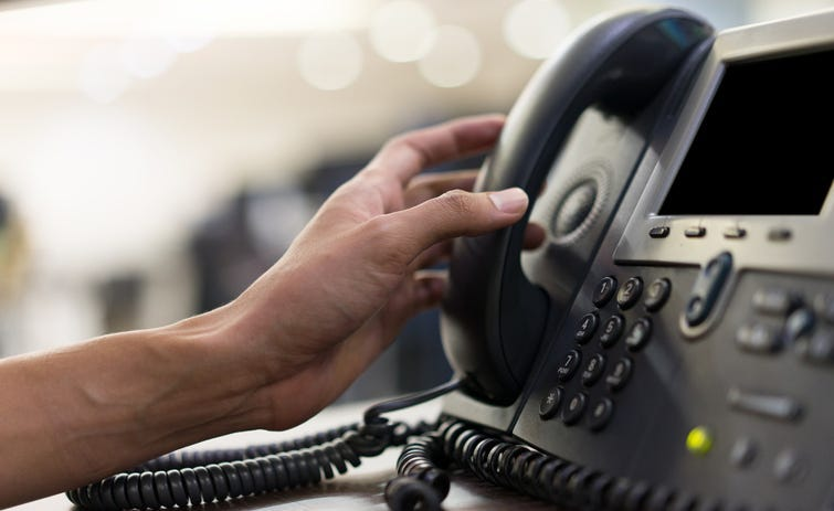 Person touching handset of telephone