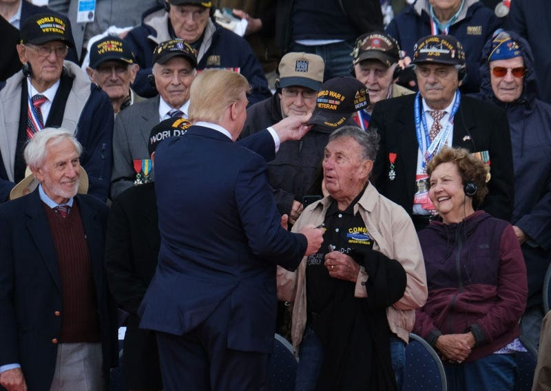President Donald Trump tips the cap of a U.S. veteran of the Battle of Normandy as other veterans look on during the main ceremony to mark the 75th anniversary of the World War II Allied D-Day invasion of Normandy at Normandy American Cemetery in 2019.