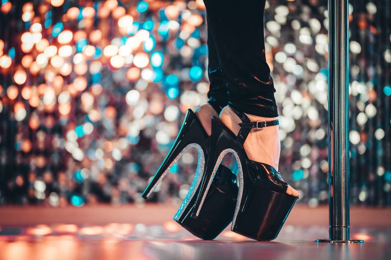 Legs in high sexy shoes near pylone. Striptease dancer moving on stage in strip night club. Pole dancing background