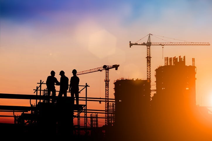 Silhouette of engineer and construction team working at site over blurred background for industry background with Light fair.Create from multiple reference images together