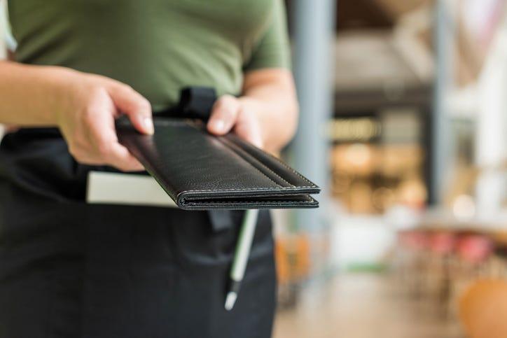 waitress offers bill at restaurant