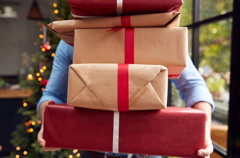 A man holds a stack of packages that obscure his face