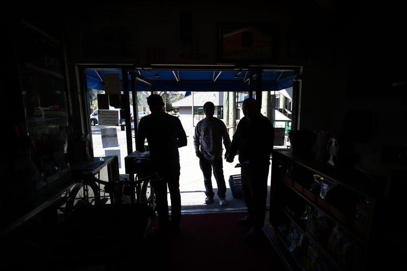 Akber Jiwani (R), the owner of New Bait Shop, and David Johnson (L), owner of Davey Jones Market, talk to a customer in front of their store darkened by a power outage on October 10, 2019 in Sausalito, California.