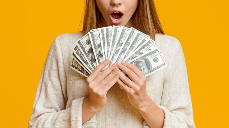 Amazed young woman holding bunch of money banknotes, celebrating profit over orange background, panorama with copy space