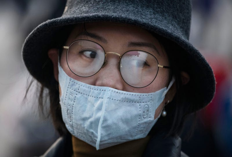 A Chinese woman's glasses fog up while wearing a protective mask at Beijing Station before she boarded a train before the annual Spring Festival on January 22, 2020 in Beijing, China.