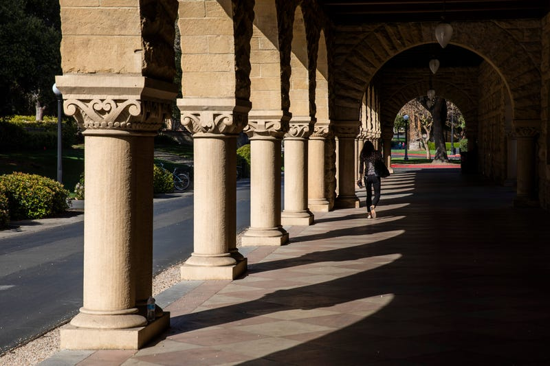 A person walks past archways during a quiet morning at Stanford University on March 9, 2020.