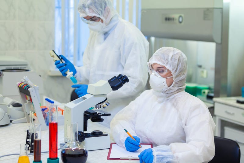 Scientists in protective suits in a science laboratory study a dangerous virus to eliminate the epidemic - stock photo