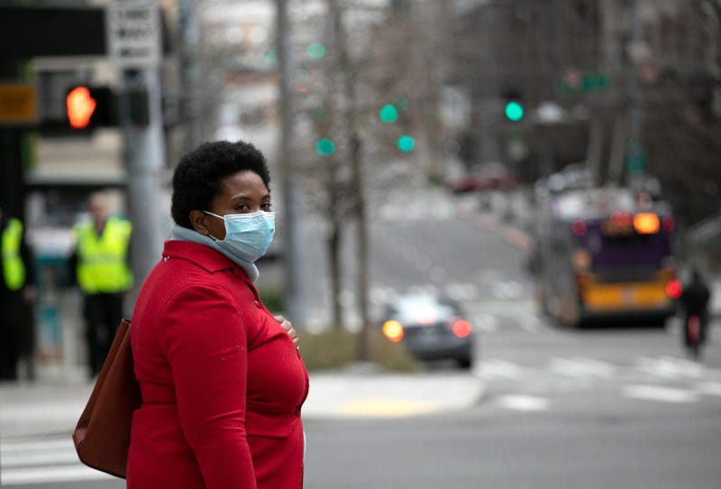A masked pedestrian pauses near the Amazon headquarters on March 10, 2020 in downtown Seattle, Washington.