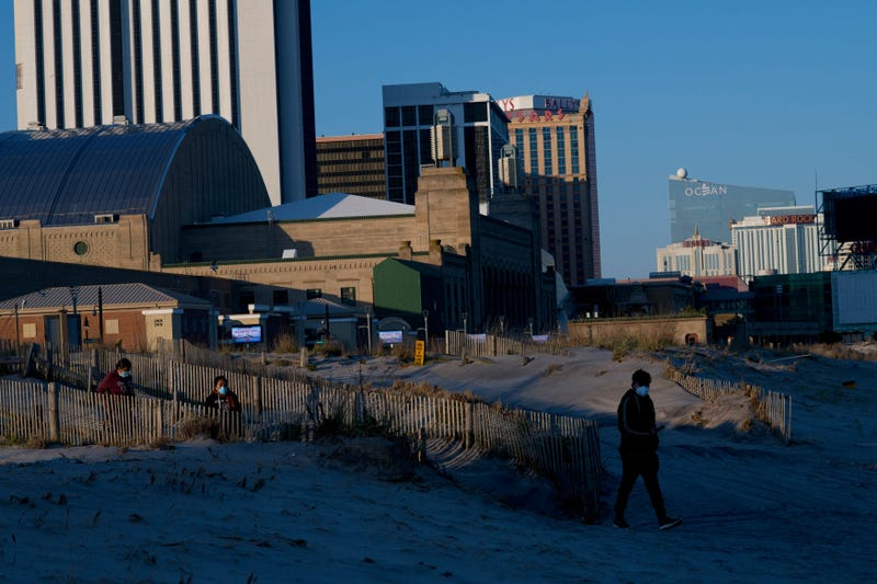 People wearing masks walk on the beach at dusk during the coronavirus pandemic on May 7, 2020 in Atlantic City, New Jersey.