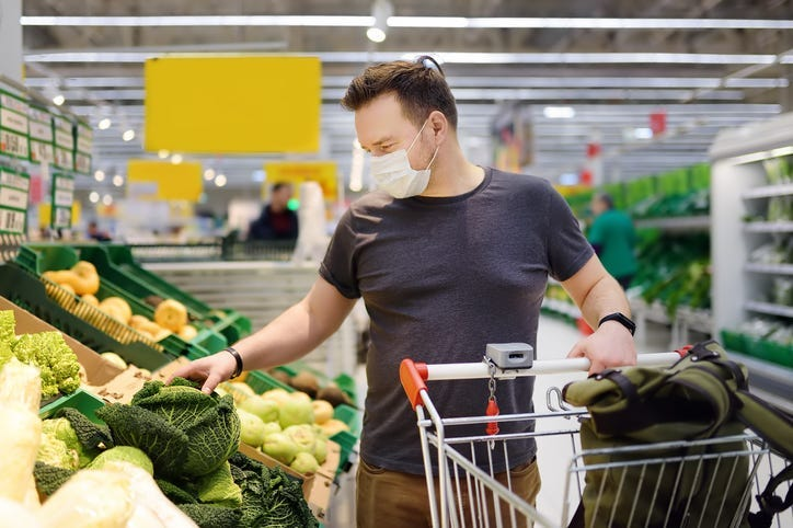 Man wearing disposable medical mask shopping in supermarket