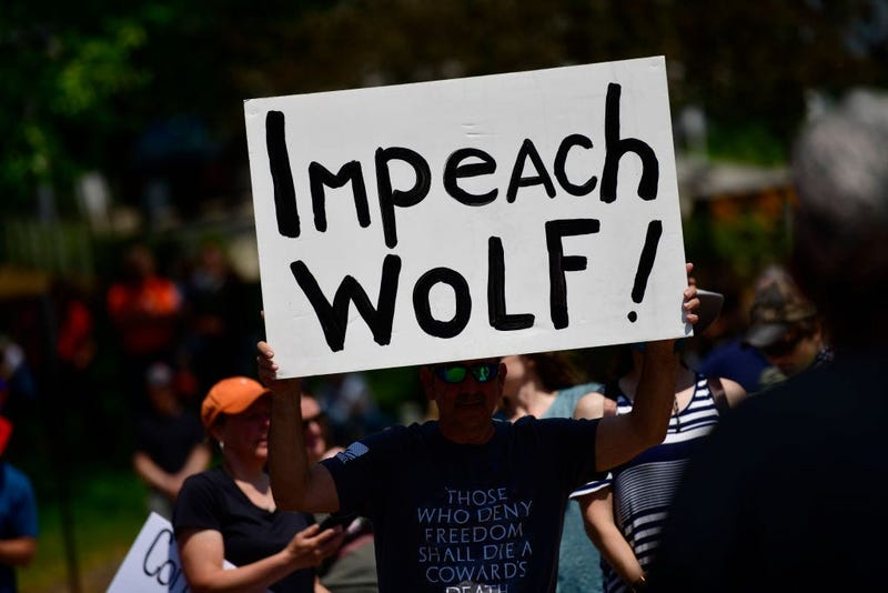 """A demonstrator holds a sign stating """"Impeach Wolf!"""" during a protest rally against Pennsylvania Governor Tom Wolf outside the State Capitol Building"""