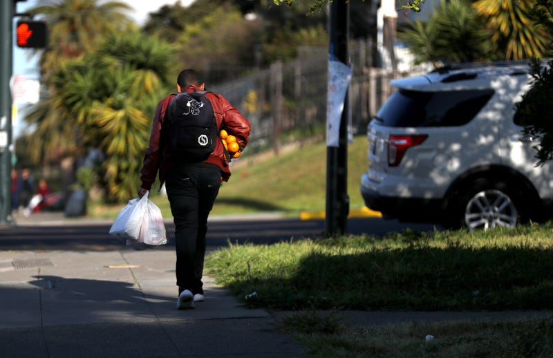 A man carries oranges and a bag of food that he received from the faculty at Garfield Elementary School on March 19, 2020 in Oakland.