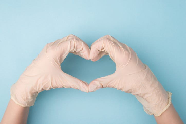 Gloved hands making a heart sign