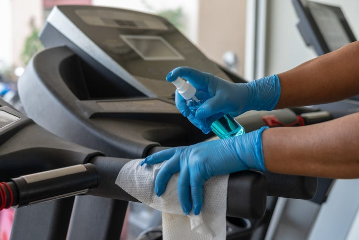 Staff using wet wipe and a blue sanitizer from the bottle to clean treadmill in gym