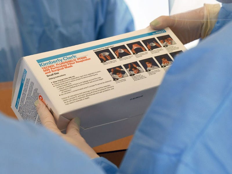 Touro University Nevada medical students check a box of N95 respirators and surgical masks.