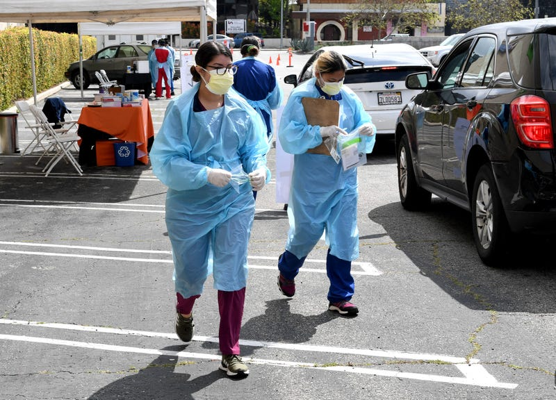 Workers wearing personal protective equipment gather COVID-19 tests administered in Los Angeles
