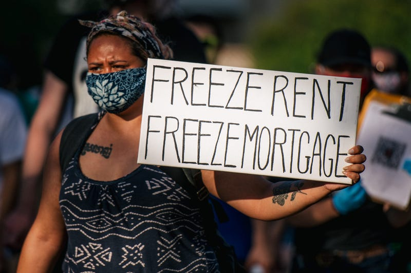 A woman holds a sign up as demonstrators march in the street during the Cancel Rent and Mortgages rally on June 30, 2020 in Minneapolis, Minnesota.