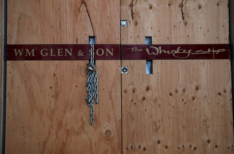 Plywood and a chain lock covers the front door of the Wm Glen & Son store on May 15, 2020 in San Francisco, California.