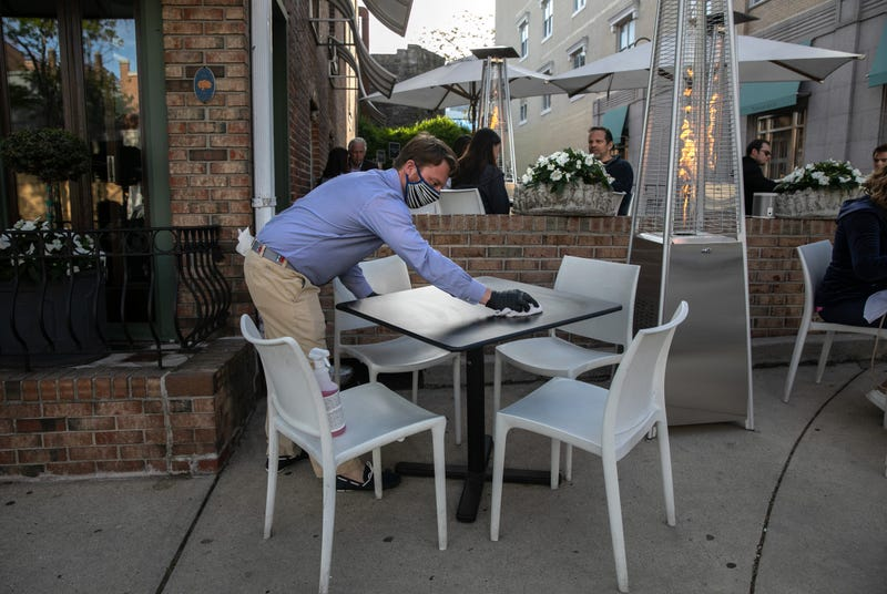 An employee at Terra restaurant cleans an outdoor table on May 20, 2020 in Greenwich, Connecticut.