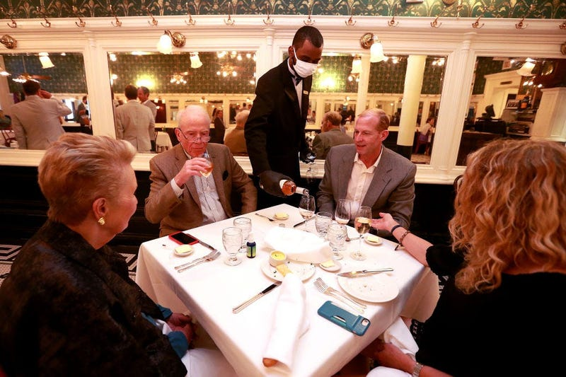 A waiter pours wine during dinner at Galatoire's Restaurant on May 22, 2020 in New Orleans, Louisiana.
