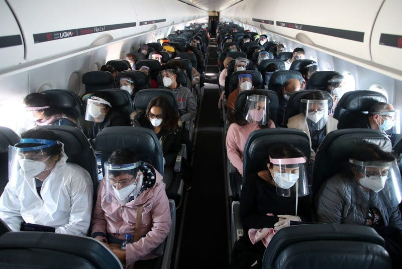 Passengers wearing face shields remain seated during the LA 2212 flight between Lima and Trujillo, Peru on July 15, 2020.