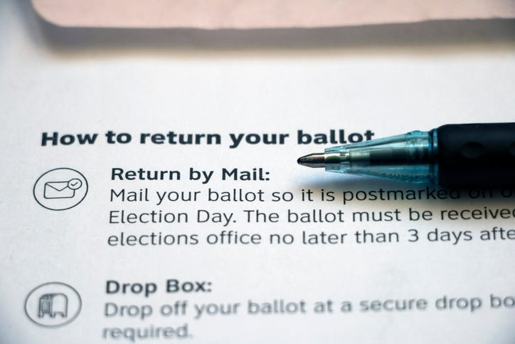 Closeup of vote-by-mail return ballot instructions on an official election mail envelope with pen lying on top.