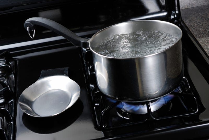 Pot of water boiling on a black natural gas stove.