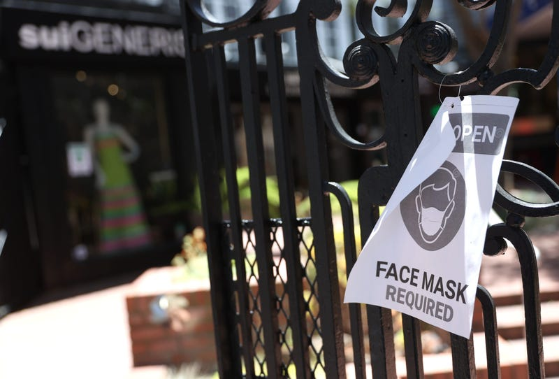 A sign alerting customers to wear a mask is posted in front of a retail store that has reopened on June 16, 2020 in San Francisco, California.