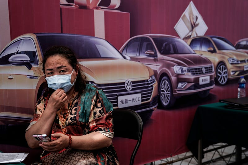 People wear face masks while visits the Auto Fair during Dragon Boat Festival holiday on June 25, 2020 in Wuhan, China.