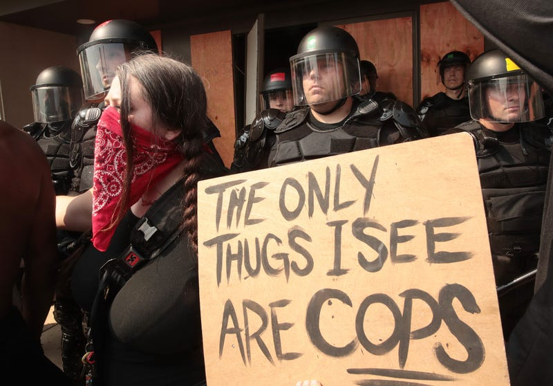 "olice stand guard as woman protests with a sign written ""the only thugs I see are cops"" the day after a Black man was shot by police causing outrage and local unrest in the city on August 24, 2020 in Kenosha, Wisconsin."
