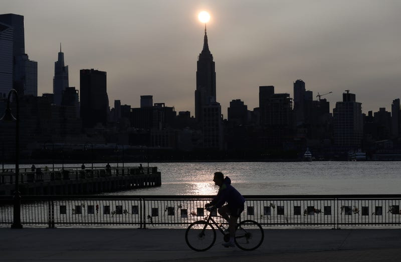 The sun rises behind the Empire State Building in New York City in a haze created by smoke from the west coast wildfires reaching the east coast of the USA on September 15, 2020 as seen from Hoboken, New Jersey.