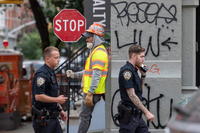NYPD officers without masks walk past a construction worker holding a stop sign as the city continues Phase 4 of re-opening following restrictions imposed to slow the spread of coronavirus on September 16, 2020 in New York City.