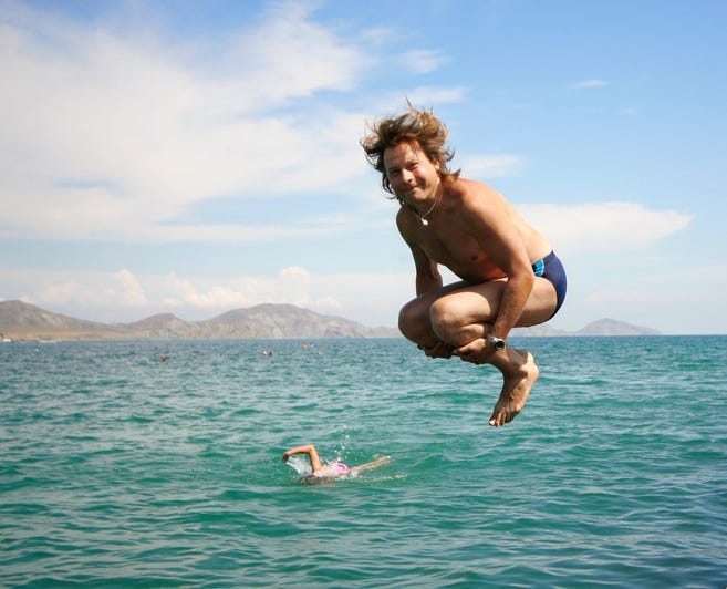 Man jumping into ocean wearing blue Speedo