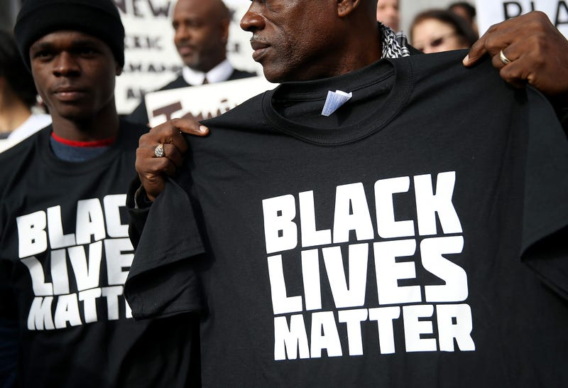 """SAN FRANCISCO, CA - DECEMBER 18: A protester holds a black lives matter t-shirt during a """"Hands Up, Don't Shoot"""" demonstration in front of the San Francisco Hall of Justice on December 18, 2014 in San Francisco, California."""