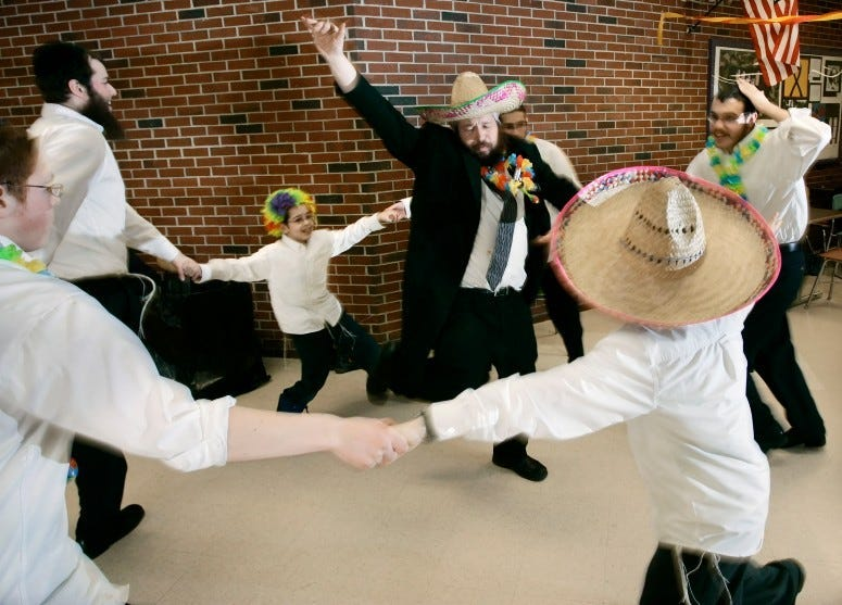 Rabbi Moshe Wilansky of Portland, center, dances with others during a Purim celebration held by Chabad of Maine at Deering High School in Portland, 2007.