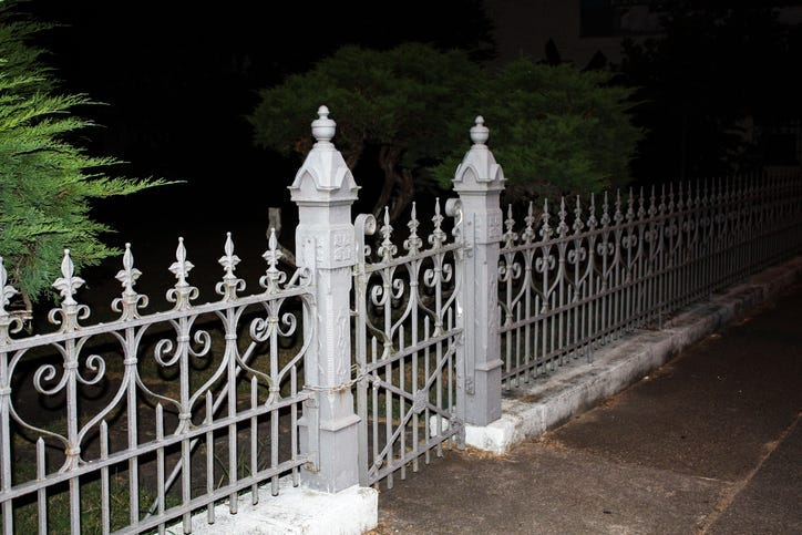 white stone or plaster fence with ornate wrought iron meeting at a creepy eerie cemetary gate with posts. taken in total darkness with one green tree on the side