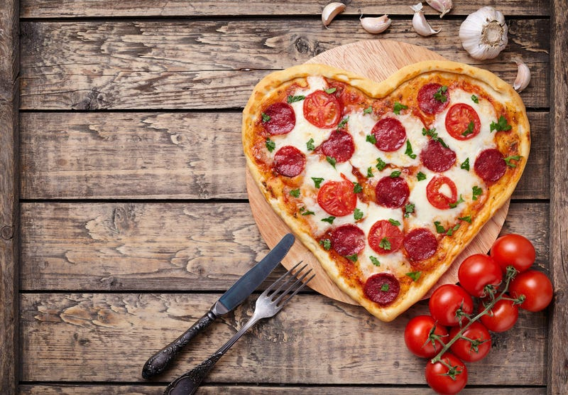Heart shaped pizza with pepperoni, tomatoes and mozzarella on vintage - stock photo
