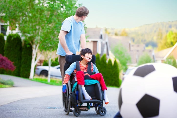 Caucasian father helping disabled son in wheelchair play soccer