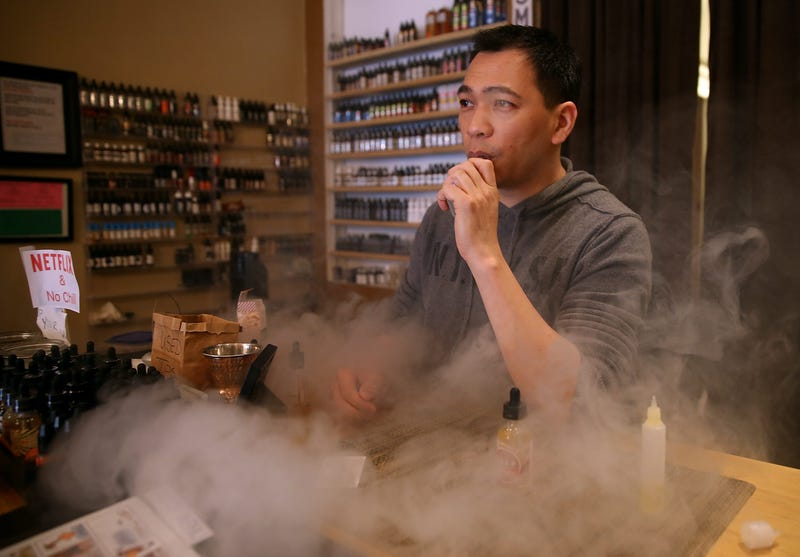 Christopher Chin blows puffs on an e-cigarette as he waits for customers at Gone With the Smoke Vapor Lounge on May 5, 2016 in San Francisco, California.