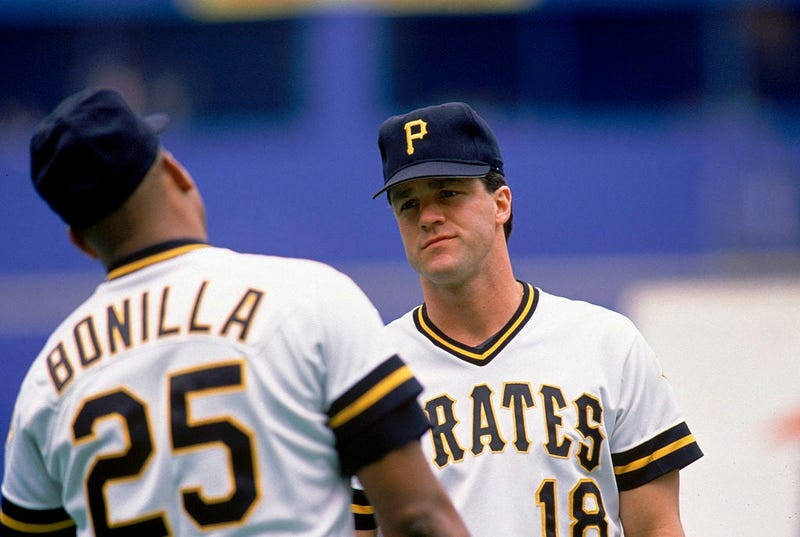 Andy Van Slyke #18 of the Pittsburgh Pirates talks with teammabte Bobby Bonilla #25 during a 1990 MLB season game at Three Rivers Stadium