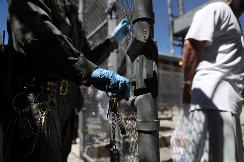 A California Department of Corrections and Rehabilitation (CDCR) officer opens the gate for a condemned inmate who is leaving the exercise yard at San Quentin State Prison's death row on August 15, 2016 in San Quentin, California.