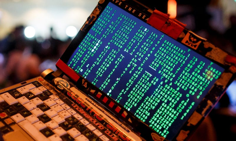 A participant poses with his laptop during the 33rd Chaos Communication Congress.