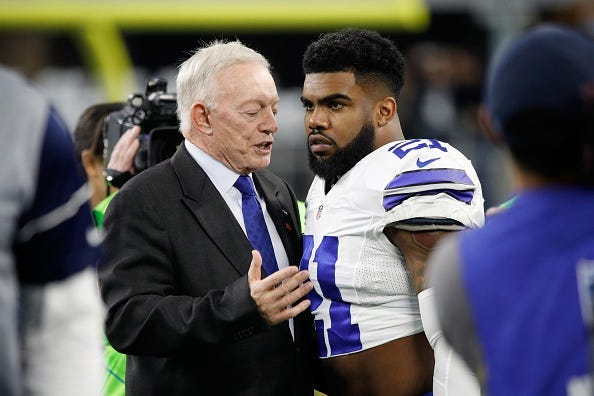 Dallas Cowboys owner Jerry Jones talks with Ezekiel Elliott #21 of the Dallas Cowboys before the NFC Divisional Playoff Game against the Green Bay Packers at AT&T Stadium on January 15, 2017 in Arlington, Texas.