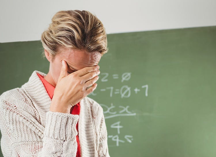 Teacher crying in front of blackboard at school